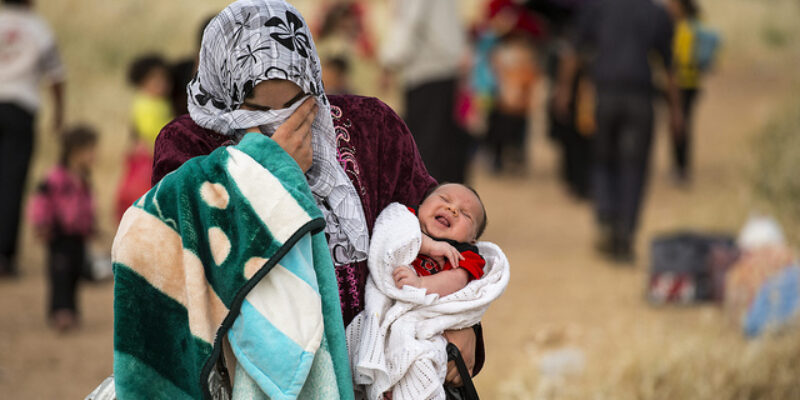 Woman covering her face with her headscarf and holding a baby