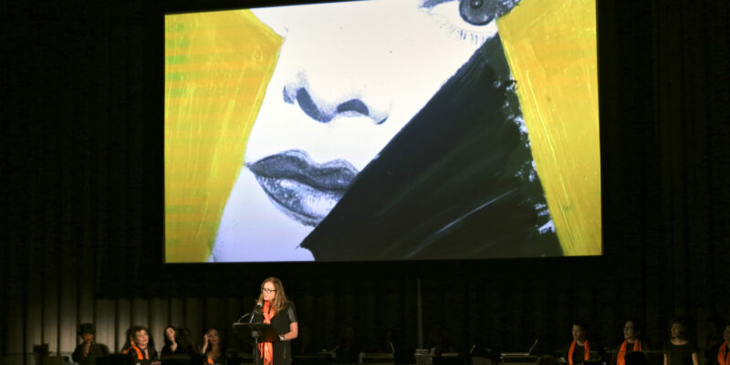 Woman stood speaking to a crowd with a projector behind her of a female face