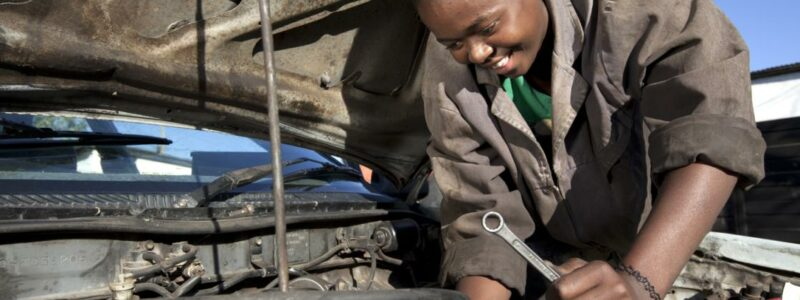 African woman working on car