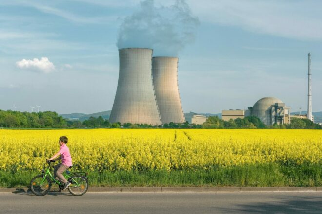 Boy on Bicycle in front of cooling towers
