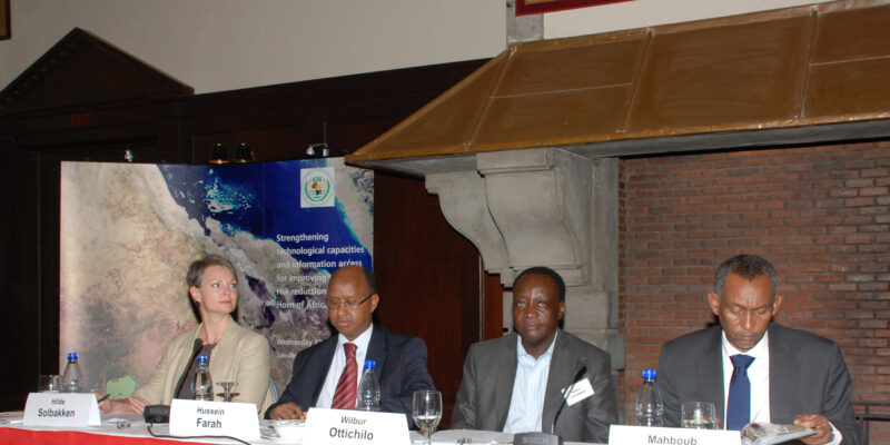 Three men and a woman sat at a speaker table in front of a banner at an event about Africa