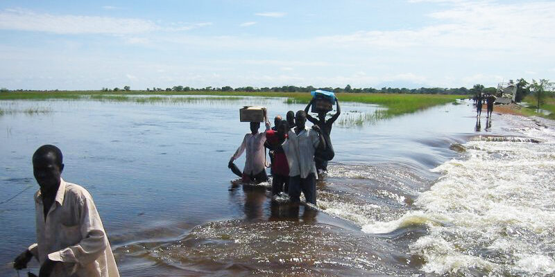 Young men wading through floodplains in Africa