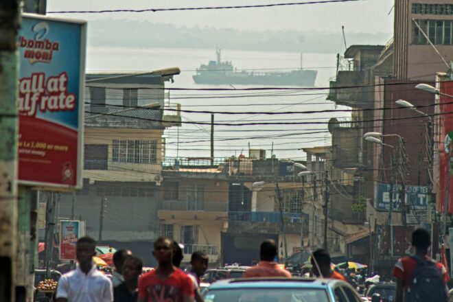 A portrait of free town with a ship at sea in the distance