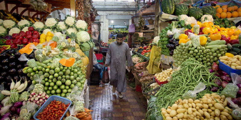 Fruit stalls in Morocco with a man walking through the centre carrying a bag