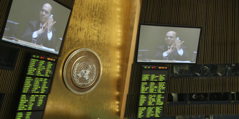 UN assembly hall with people seated watching a speaker on screen