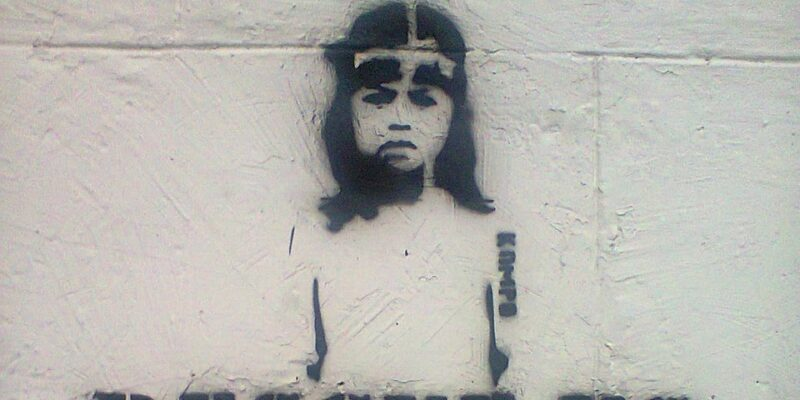 Graffiti image of a boy on a wall with text saying Rescue Us
