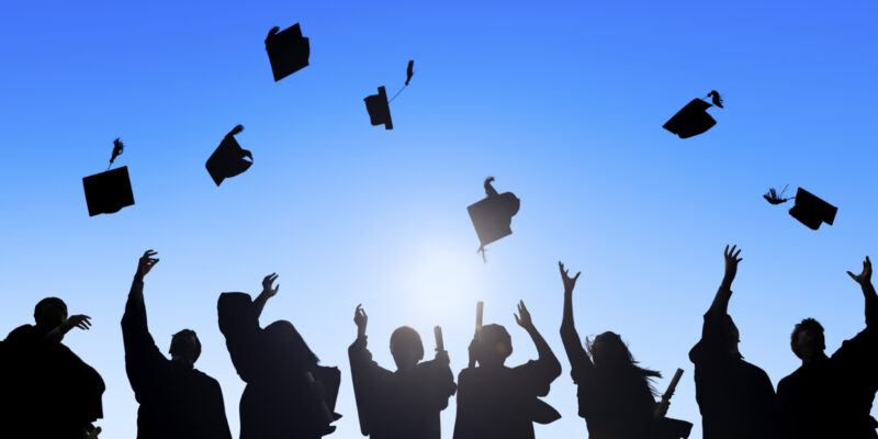 Silhouette of students celebrating their graduation by throwing their hats into the air