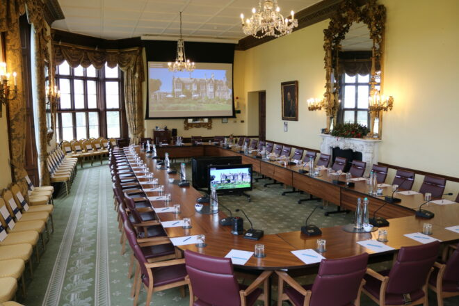 Wilton Park's conference room with table, chairs, project screen and monitor