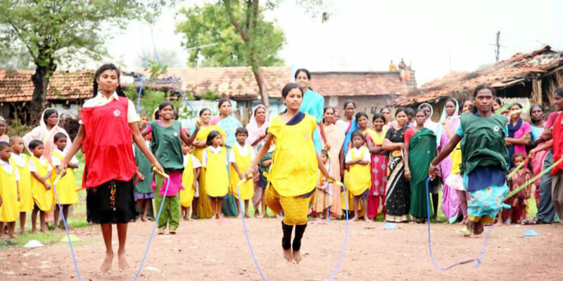 School girls skipping in India with other children and adults watching