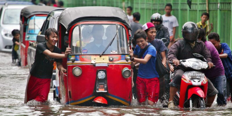 People pushing a red rickshaw through flooded streets in Jakarta