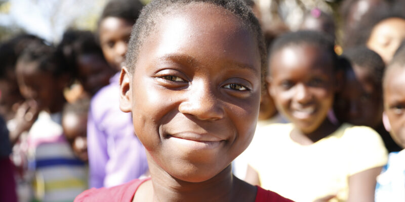 A child smiling in the forefront with more smiling children in the background
