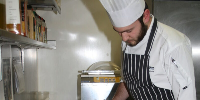 Chef using a blow torch on a tray of Crème Brulee