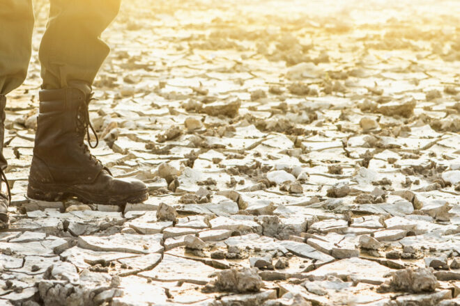 Military boots on dry lake bed climate change