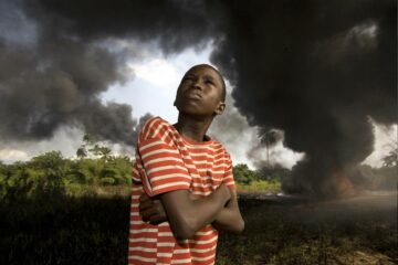 Boy wearing red and white striped t-shirt looking up at a stormy sky