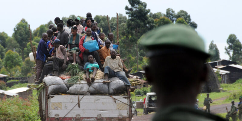 People on the back of a vehicle driving away from a soldier who is watching