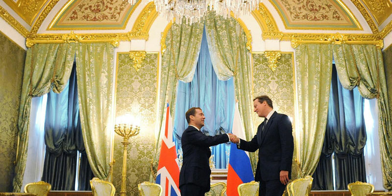 Former Prime Minister David Cameron meeting Russian President Dmitry Medvedev in a grand setting with gold furnishing