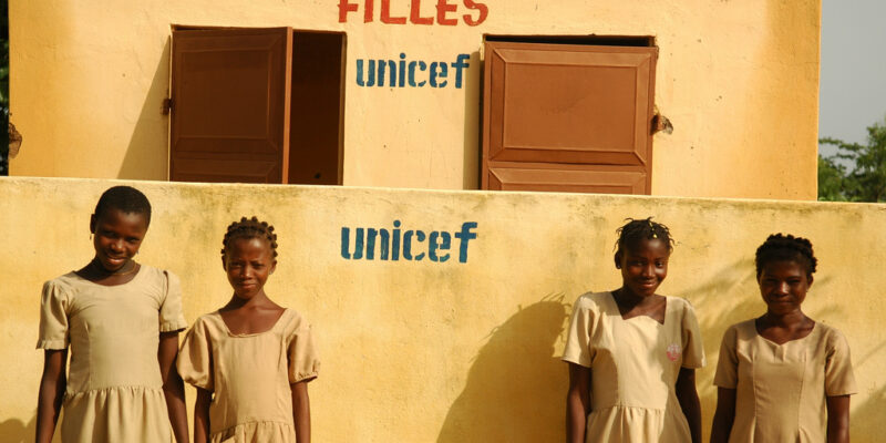 School girls stand outside a newly built block of girls toilets in Togo