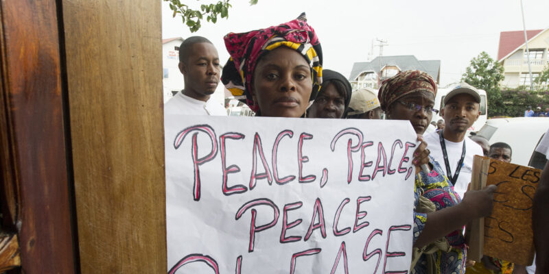 People of the DRC holding a sign saying Peace, Peace, Peace, Please