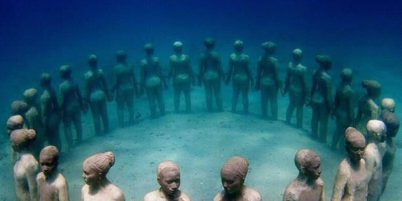 Stone figures stood in a circle holding hands and facing outwards as a tribute to slaves