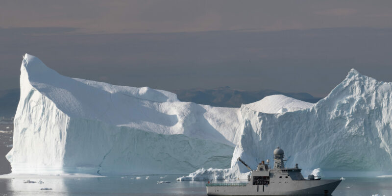 Military ship floating in an ice field