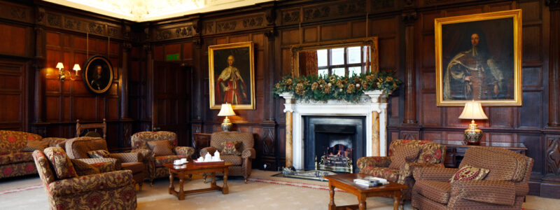 Wilton Park's Common Room with chairs and tables arranged around the fireplace