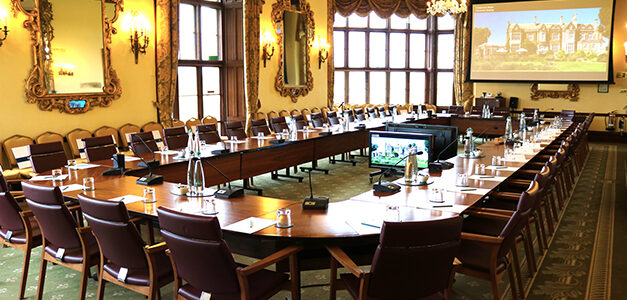 Wilton Park's conference room with a large conference table, chairs, a projector screen and a monitor