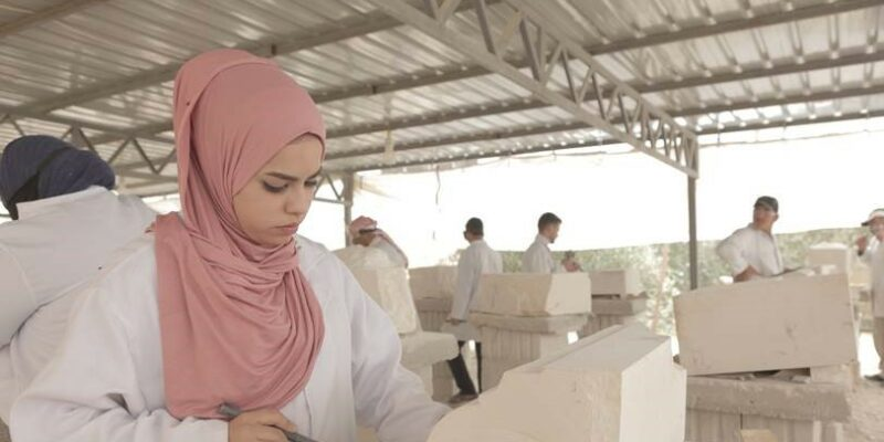 Woman wearing headscarf using tools to carve white stone