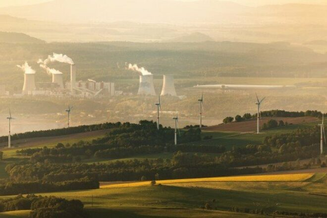 Faint view of chimneys with smoke in the background, with a more vibrant view of a wind farm in the foreground