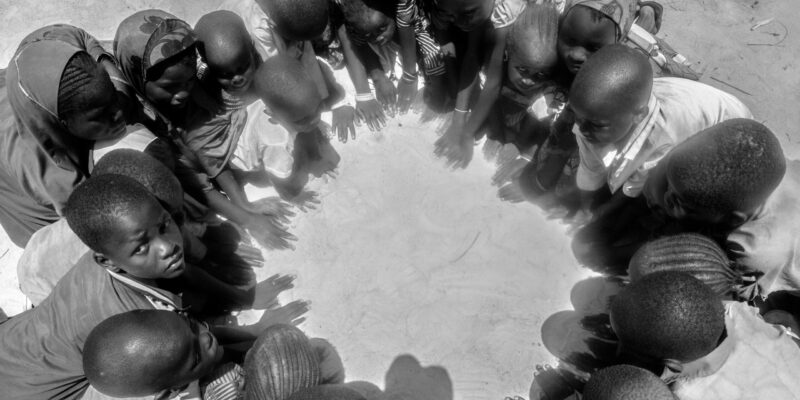A group of Nigerian children sat in a circle